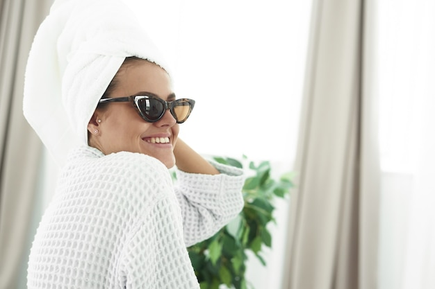 Młoda kobieta w szlafroku, z białym ręcznikiem na głowie i czarnymi okularami przeciwsłonecznymi, patrząc w lustro w łazience.