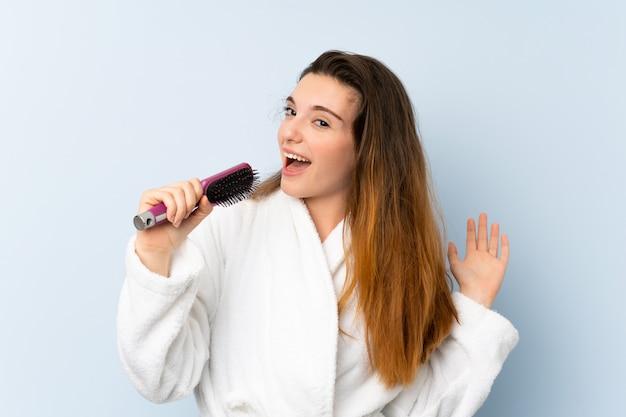Młoda kobieta w szlafroku z grzebieniem do włosów i śpiewem