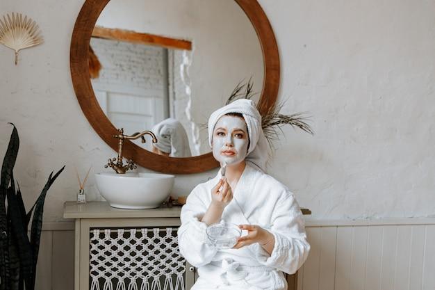 Młoda kobieta w szlafroku z ręcznikiem owiniętym wokół głowy nakłada maskę na twarz w łazience.