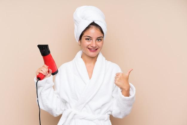 Młoda kobieta w szlafroku z suszarką do włosów na izolowanej ścianie z kciukami do góry, ponieważ stało się coś dobrego