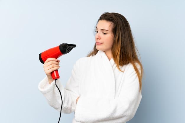 Młoda kobieta w szlafroku z suszarką do włosów