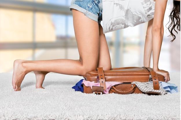 Młoda kobieta w szortach siedzi na walizce