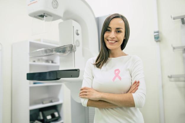 Młoda kobieta w szpitalu z różową wstążką, symbol miesiąca świadomości raka piersi.