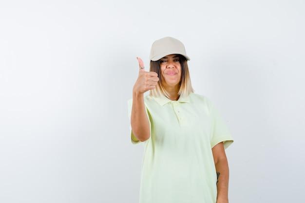 Młoda kobieta w t-shirt, czapka pokazując kciuk i patrząc wesoło, widok z przodu.
