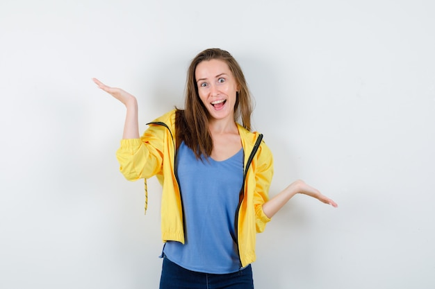 Młoda kobieta w t-shirt, kurtka co gest wagi i patrząc pewnie, widok z przodu.