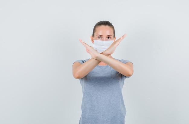 Młoda kobieta w t-shirt, maska pokazująca gest stop i patrząc poważny, przedni widok.
