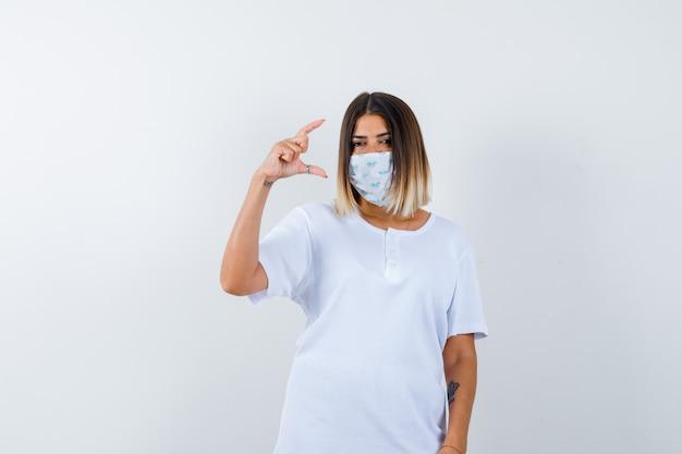 Młoda kobieta w t-shirt, maska pokazująca znak rozmiaru i wyglądająca pewnie, widok z przodu.