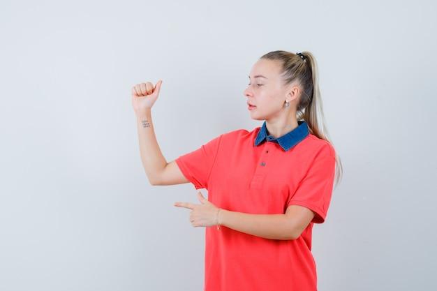 Młoda kobieta w t-shirt podnosząc ramię, wskazując w bok i patrząc skupiony