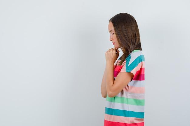 Młoda kobieta w t-shirt, ściskając ręce w geście modlitwy i patrząc z nadzieją.