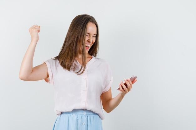Młoda kobieta w t-shirt, spódnica patrząc na telefon komórkowy z gestem zwycięzcy i szczęśliwy, widok z przodu.