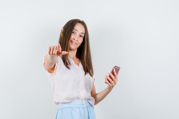 Młoda kobieta w t-shirt, spódnica, trzymając telefon komórkowy i wskazując na aparat, widok z przodu.