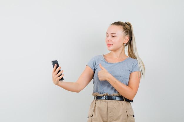 Młoda kobieta w t-shirt, spodnie pokazując kciuk do góry na czacie wideo i patrząc wesoło, widok z przodu.
