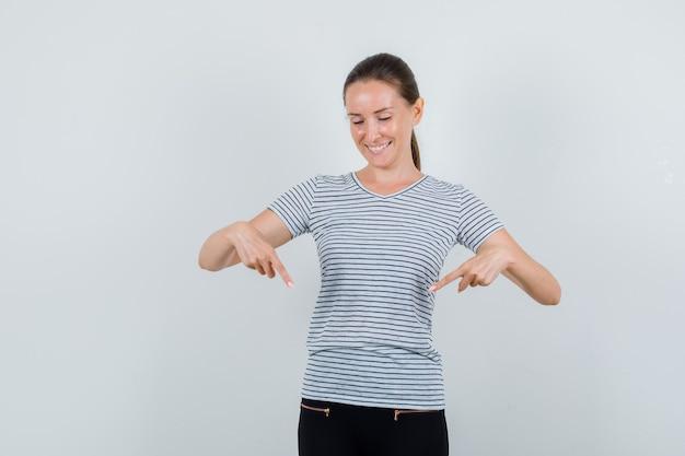 Młoda kobieta w t-shirt, spodnie skierowaną w dół i patrząc wesoło, widok z przodu.