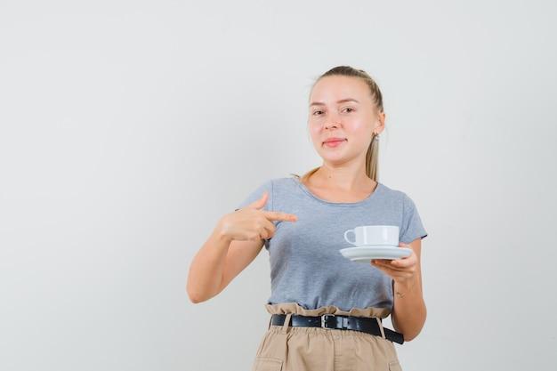 Młoda kobieta w t-shirt, spodnie, wskazując przy filiżance napoju i patrząc zadowolony, widok z przodu.