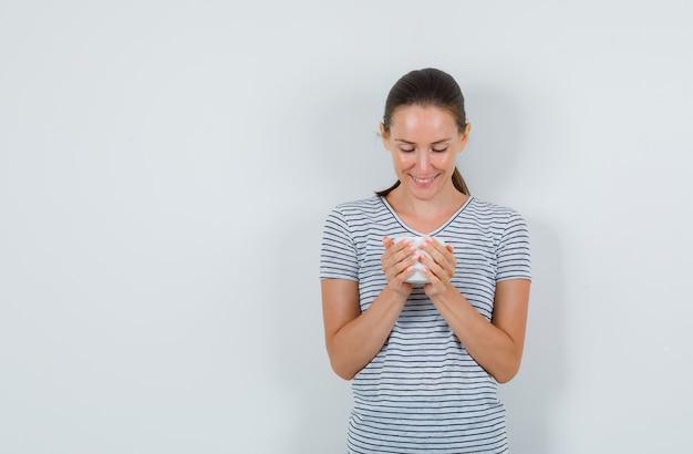 Młoda kobieta w t-shirt, trzymając filiżankę herbaty i patrząc wesoło, widok z przodu.