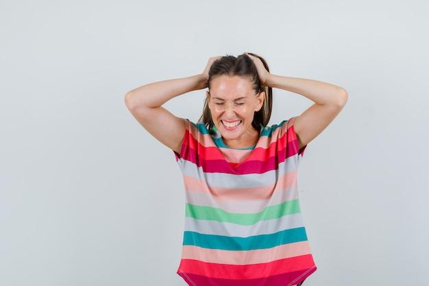 Młoda kobieta w t-shirt, trzymając się za ręce na włosy i patrząc szczęśliwy, widok z przodu.