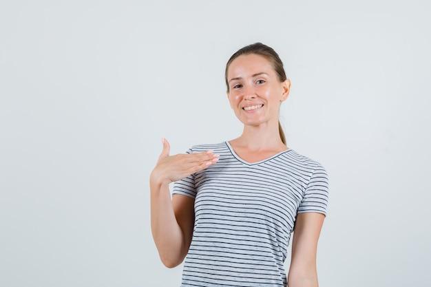 Młoda kobieta w t-shirt w paski, wskazując na siebie i patrząc pewnie, widok z przodu.