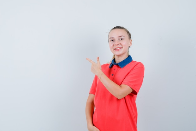 Młoda kobieta w t-shirt, wskazując na lewym górnym rogu i patrząc zadowolony