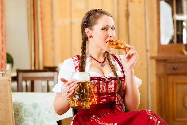 Młoda kobieta w tradycyjnym bawarskim tracht w restauracji lub pubie