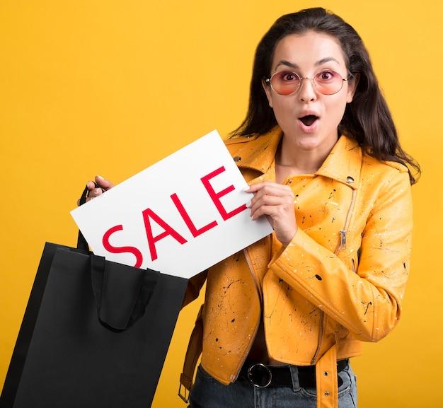 Młoda kobieta w transparent sprzedaży żółtej skórzanej kurtki
