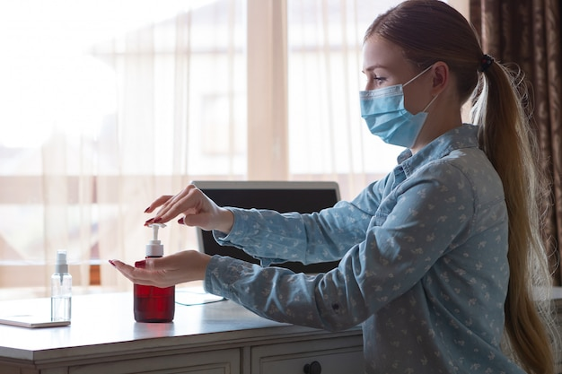 Młoda kobieta w twarzy maski dezynfekujące gadżety ukazuje się na jej miejscu pracy