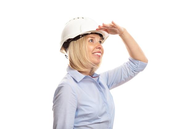 Młoda kobieta w ubrania biurowe i kask budowy wygląda na odległość