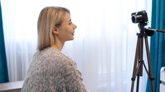 Młoda kobieta w ubranie nagrywa się w aparacie na statywie. widok z boku. wesoła blogerka nagrywająca wideo w domu