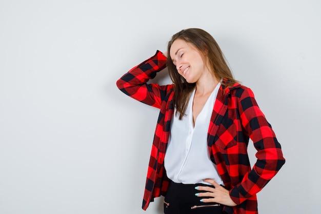 Młoda kobieta w ubraniu z ręką na głowie i patrząc spokojnie, widok z przodu.