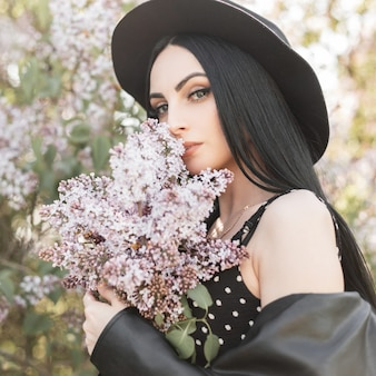 Młoda kobieta w ukwieconym parku spoczywa na łonie natury. modna dziewczyna w eleganckim kapeluszu w modnej czarnej sukience i wiosennych kwiatach bzu na zewnątrz. wspaniała dama wącha niesamowity bukiet kwiatów. słoneczny świeży portret