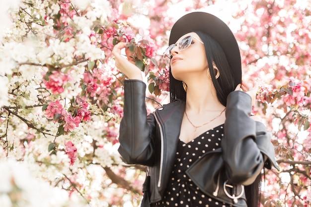Młoda kobieta w ukwieconym parku spoczywa na łonie natury. modna dziewczyna w eleganckim kapeluszu w modnych okularach przeciwsłonecznych w czarnym stroju i różowe wiosenne kwiaty na zewnątrz. luksusowa dama wącha niesamowite kwitnące drzewo.