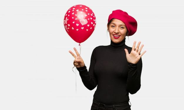 Młoda kobieta w valentines dniu pokazuje liczbę siedem