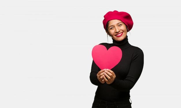 Młoda kobieta w valentines dniu robi kierowemu kształtowi z rękami