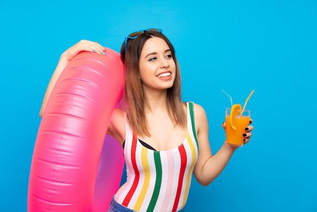 Młoda kobieta w wakacje letnie nad niebieską ścianą przy koktajlu