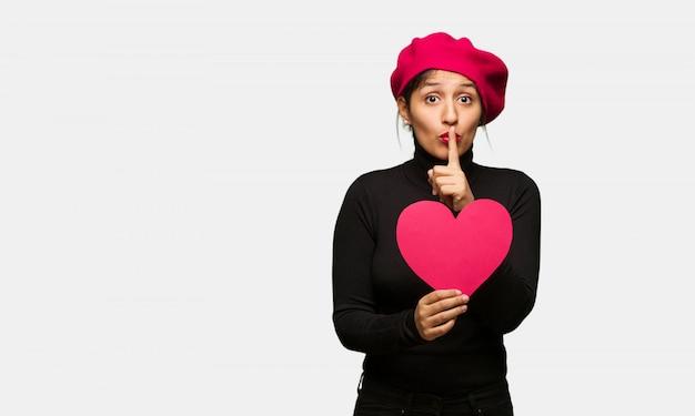 Młoda kobieta w walentynki trzyma w tajemnicy lub prosząc o ciszę