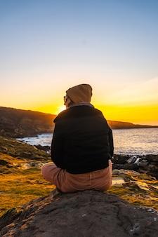 Młoda kobieta w wełnianej czapce relaksująca się zimą, oglądając zachód słońca na górze jaizkibel w miejscowości pasajes, gipuzkoa