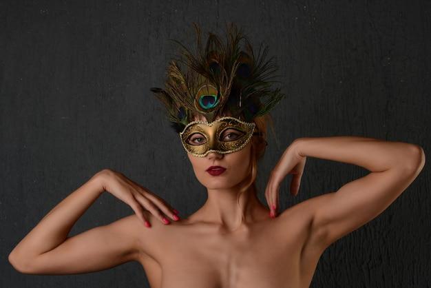 Młoda kobieta w weneckiej masce karnawałowej zbliżenie portret kobiety. ciemne tło