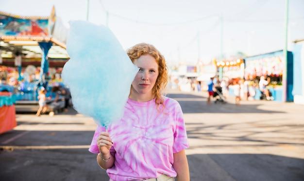 Młoda kobieta w wesołym miasteczku z watą cukrową