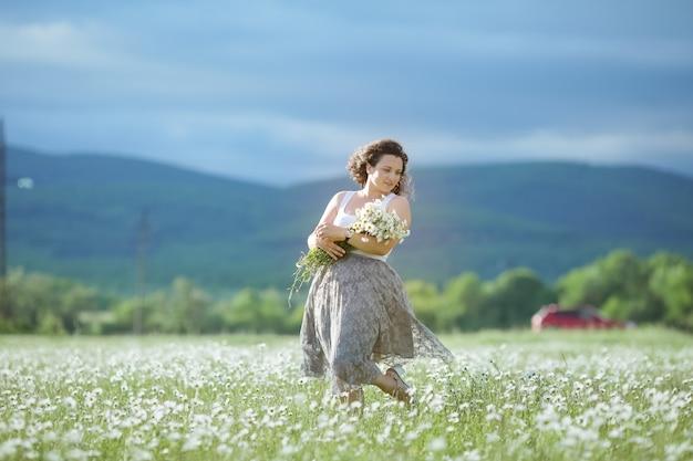 Młoda kobieta w wieku 30 lat w spódnicy zbiera stokrotki na polu