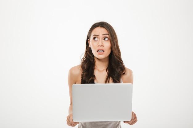 Młoda kobieta w wieku 30s, odwracając wzrok, jest zestresowana lub rozczarowana podczas korzystania ze srebrnego notesu w ręku, odizolowane na białej ścianie