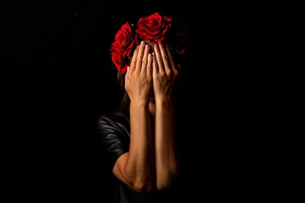Młoda kobieta w wieńcu z kwiatów, zasłaniająca twarz dłońmi