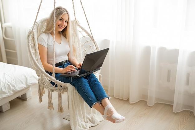 Młoda kobieta w wiszącym krześle z laptopem