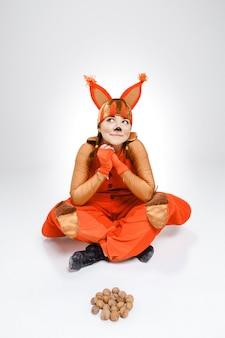 Młoda kobieta w wizerunku czerwona wiewiórka z orzechami włoskimi