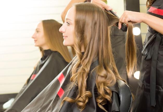 Młoda kobieta w zakładzie fryzjerskim robi loki lokówką.