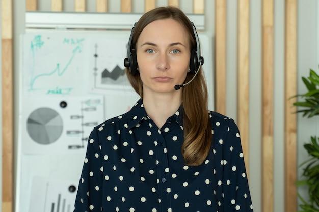 Młoda kobieta w zestawie słuchawkowym stojąca w biurze, pracująca jako call center lub operator usług wsparcia, patrzy w kamerę