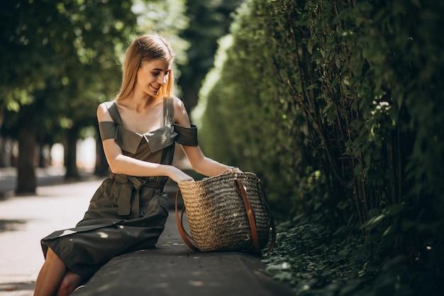 Młoda kobieta w zieleni sukni obsiadaniu w parku