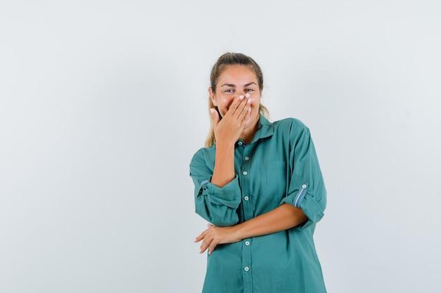Młoda kobieta w zielonej bluzce obejmującej usta ręką, śmiejąc się i patrząc słodko