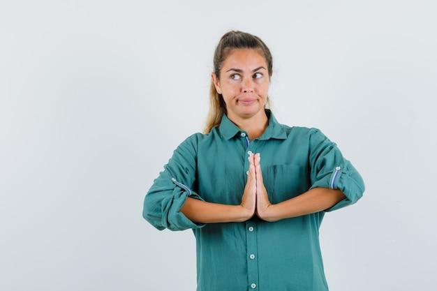 Młoda kobieta w zielonej bluzce pokazuje gest namaste i patrzy zamyślony