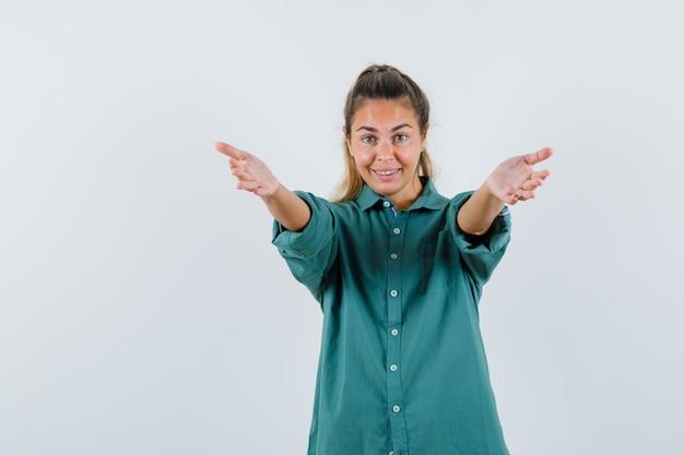 Młoda kobieta w zielonej bluzce zaprasza do przyjścia i szuka szczęśliwy
