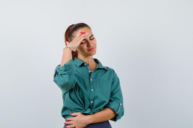 Młoda kobieta w zielonej koszuli cierpi na migrenę i wygląda na zirytowaną, widok z przodu.