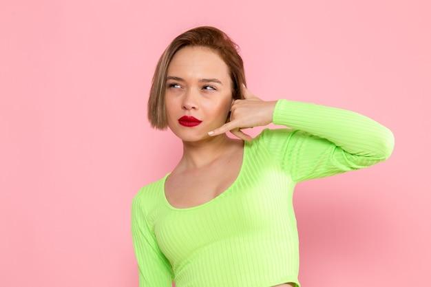 Młoda kobieta w zielonej koszuli i szare spodnie rozmowa telefoniczna pozowanie